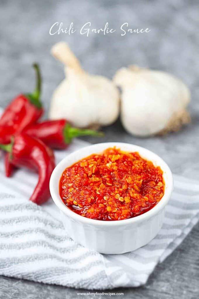 homemade Chinese chili garlic sauce in the white container with chili and garlic background