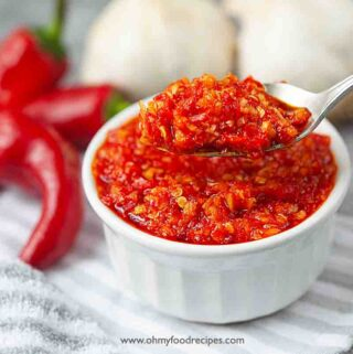 homemade Chinese chili garlic sauce scoop on a silver spoon