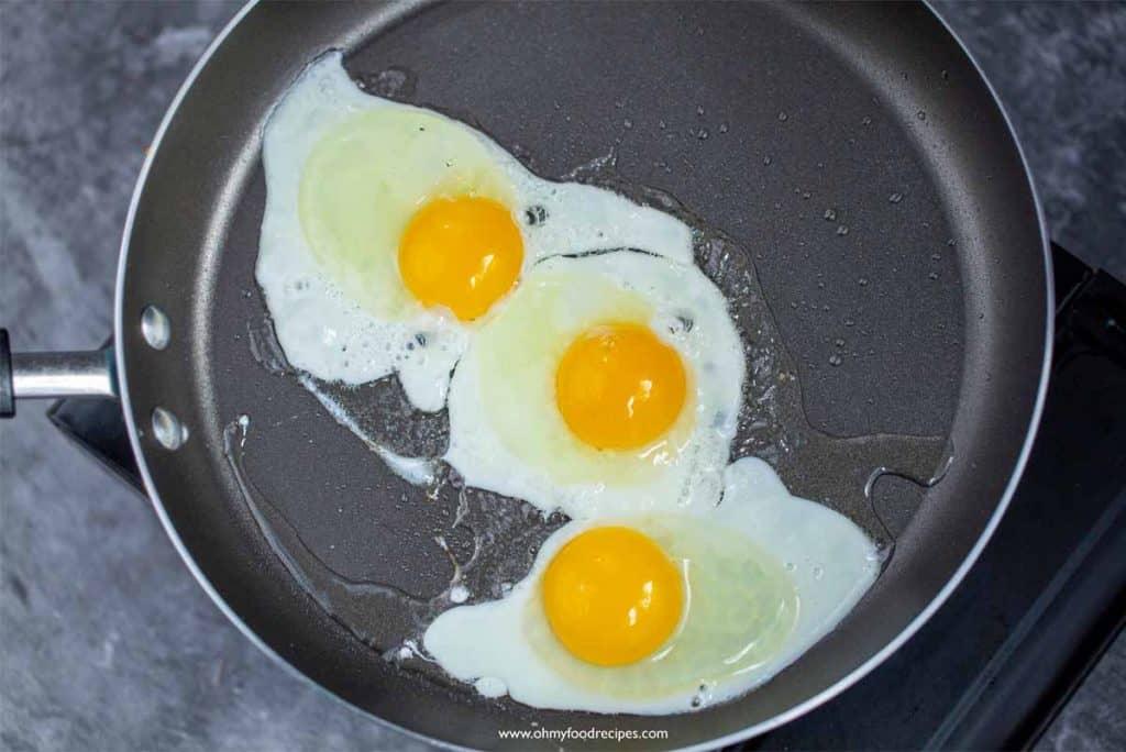 pan fried three eggs in a pan
