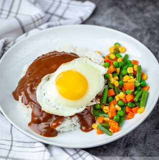 Hawaiian dish loco moco with vegetables on a white plate
