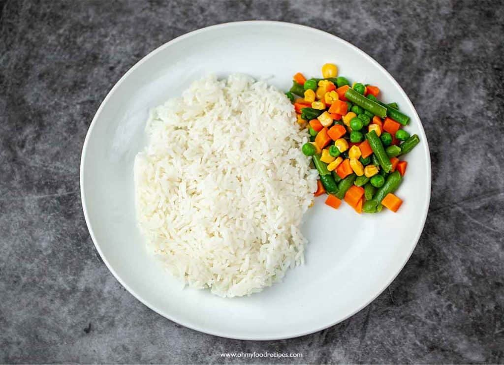 cooked rice and mixed vegetables on the white plate