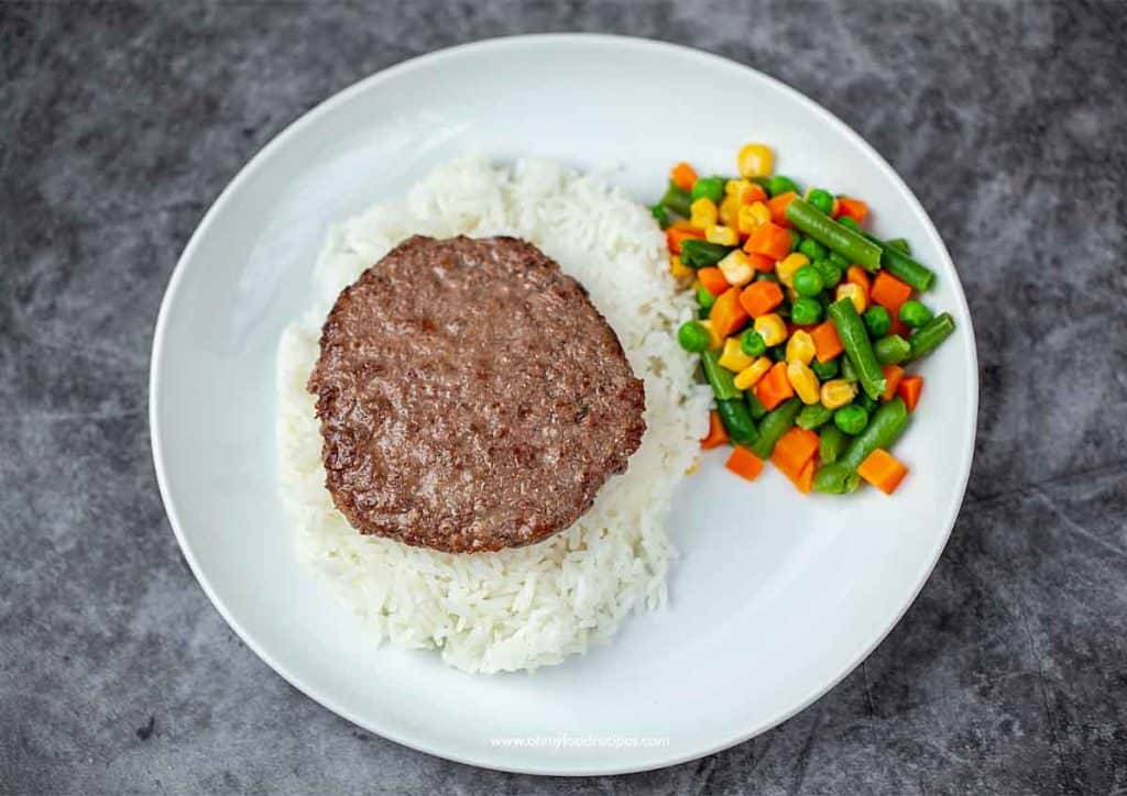 beef patty on the white rice with mixed vegetables on the side (Loco Moco Hawaiian dish)