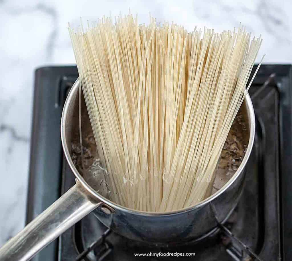 boiling rice noodles in a pot over the stove