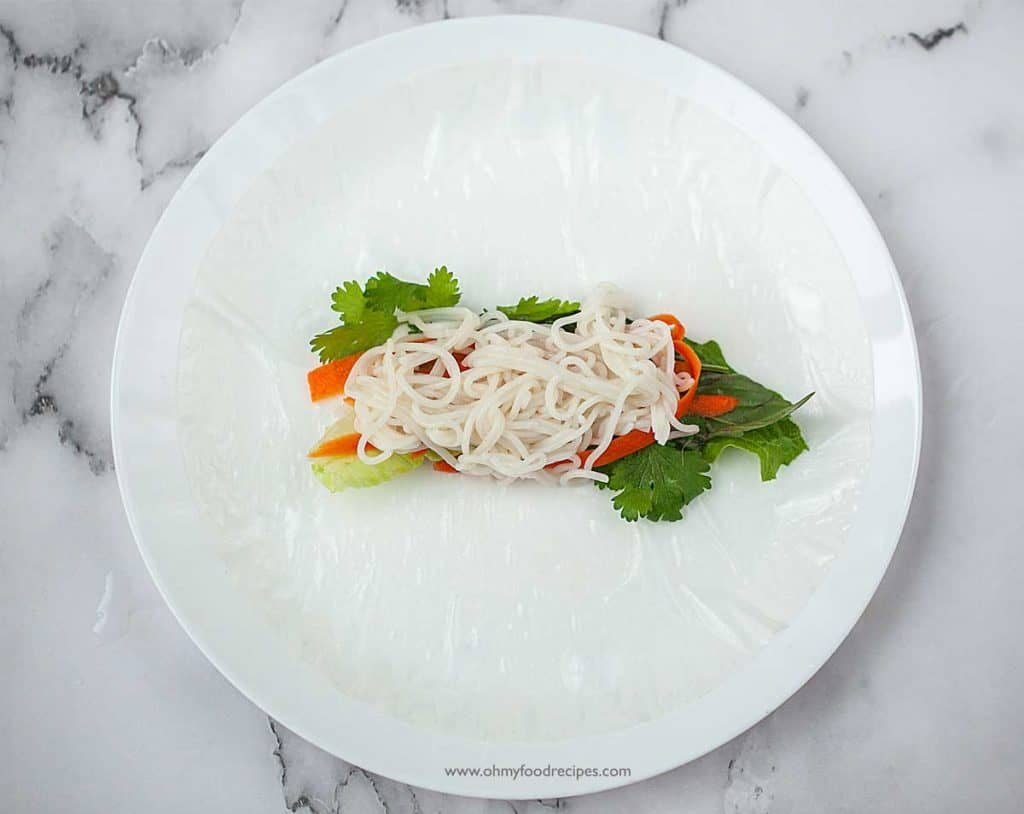 cooked rice noodles on top of the vegetable on the soaked rice paper Vietnamese spring rolls