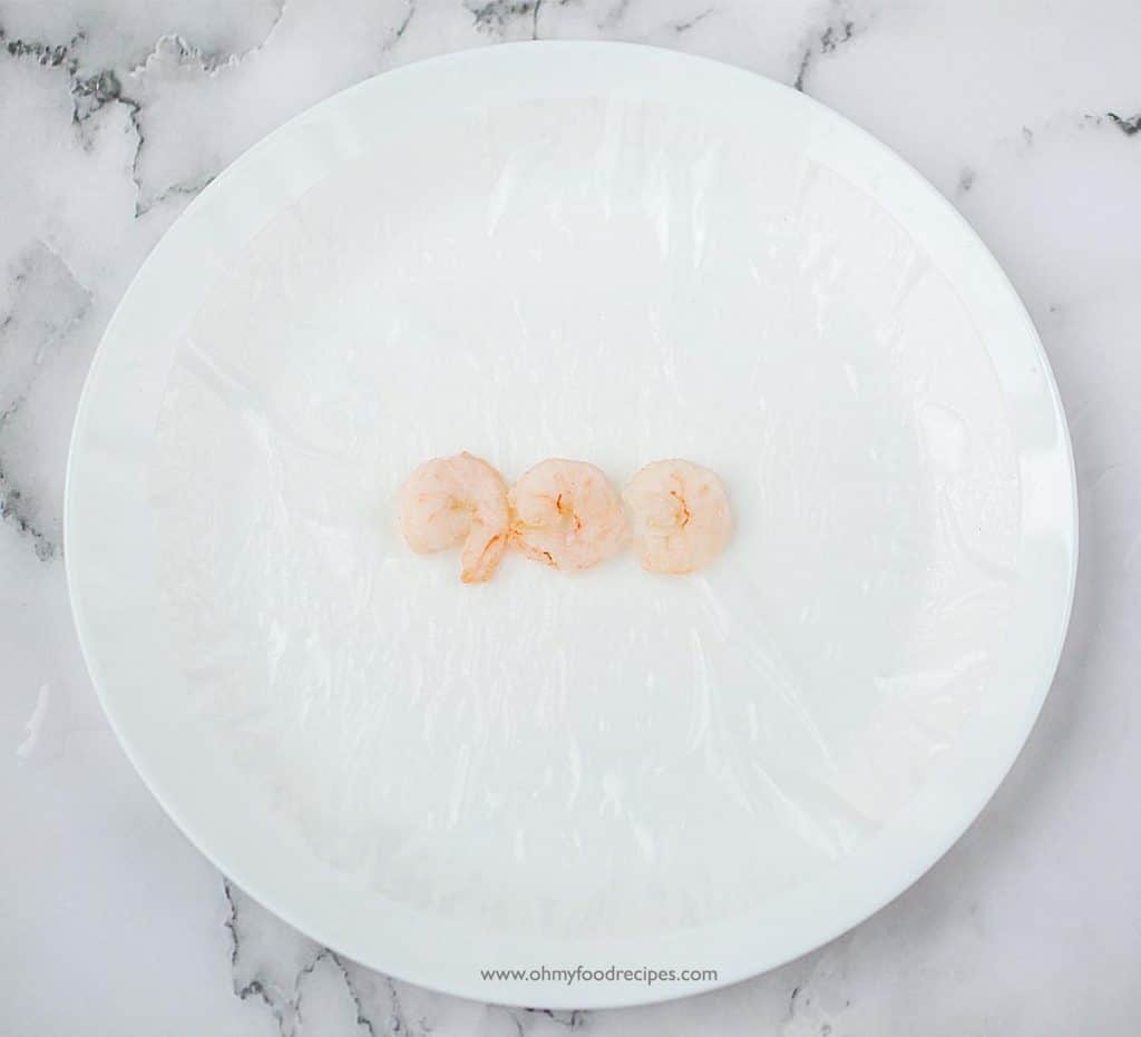 three cooked shrimp in the middle of the soaked rice paper on a white plate
