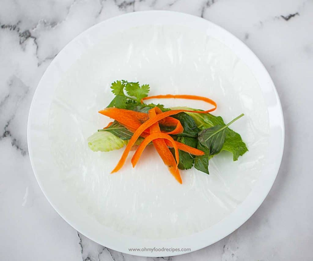 vegetables lay on the soaked rice paper on the white plate Vietnamese fresh rolls