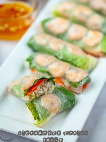 Vietnamese spring rolls one cut open on a long white plate