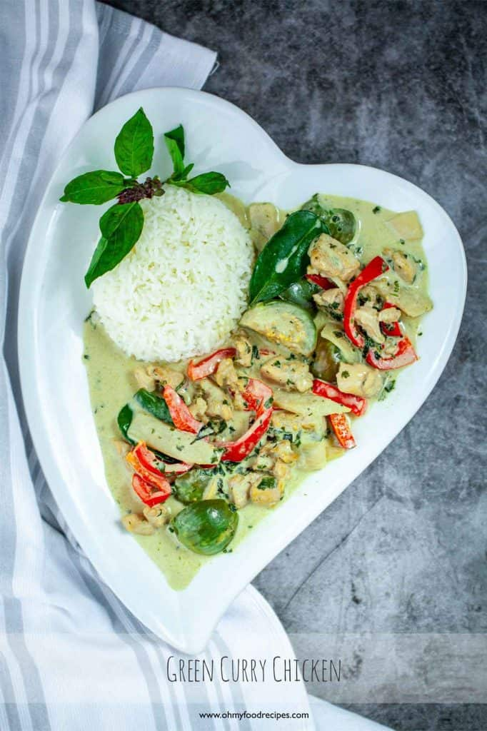 Green curry chicken serve with rice on a heart shaped white plate
