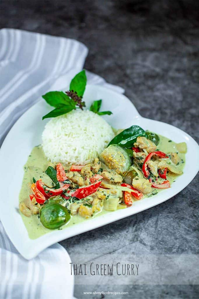 Thai green chicken curry on the white heart shaped plate with rice