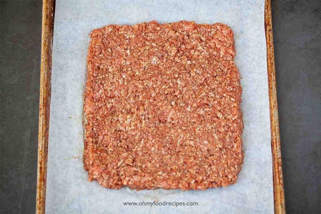 lay flat marinated ground pork on the parchment paper on the cookie sheet