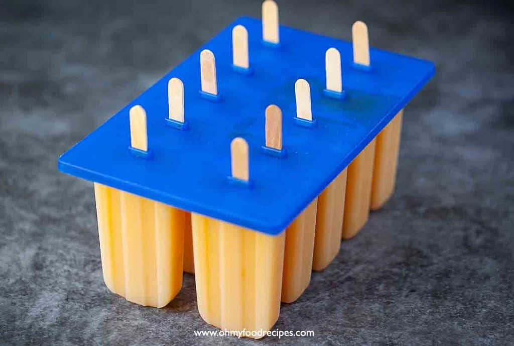 mango mixture in the popsicle mold with popsicle sticks insert
