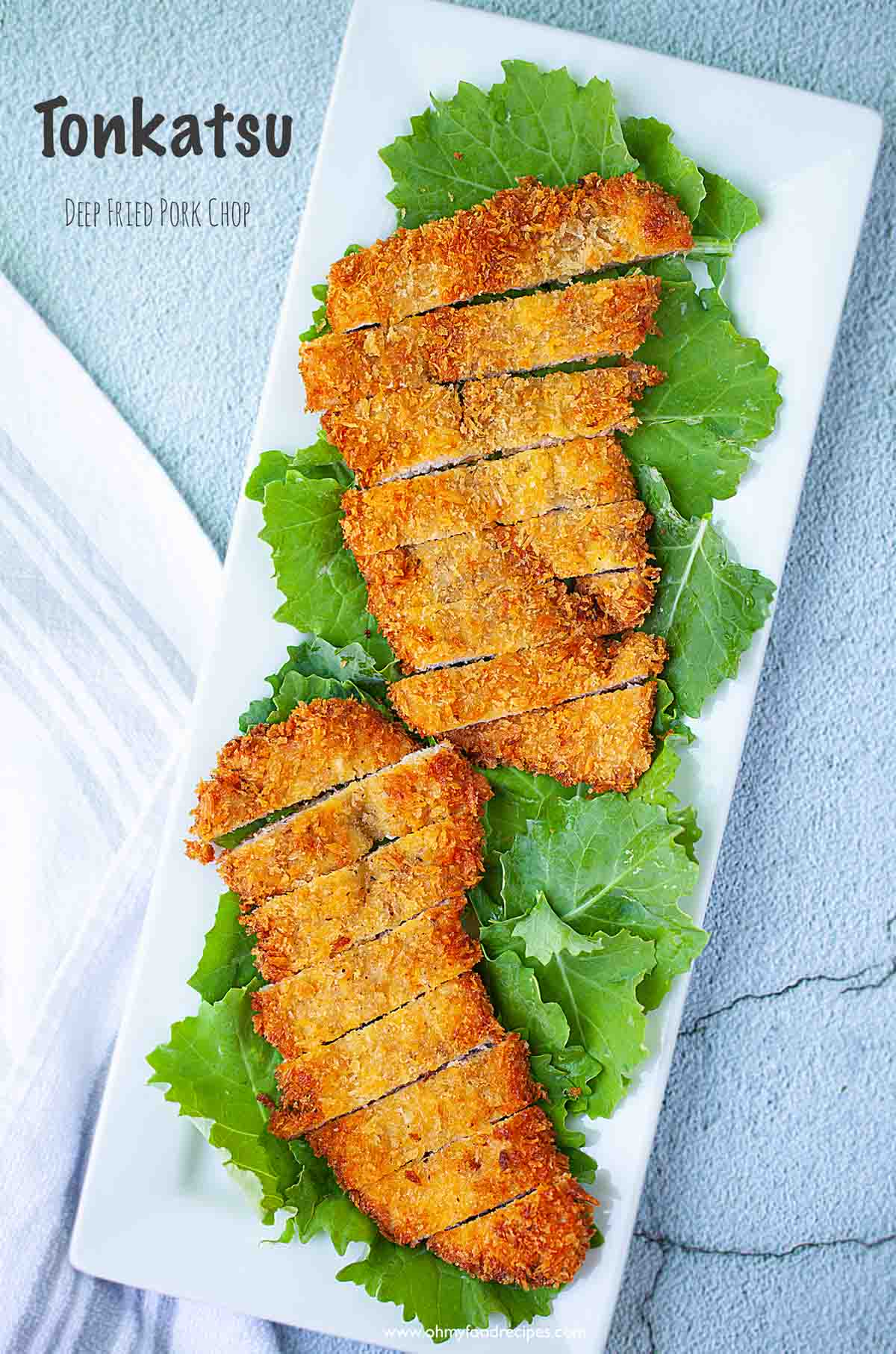 Japanese tonkatsu deep fried pork cutlets cut up on kale top view