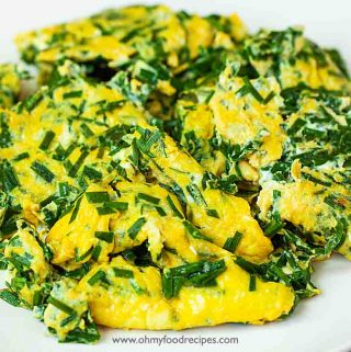 garlic chives and eggs stir fry on a white plate