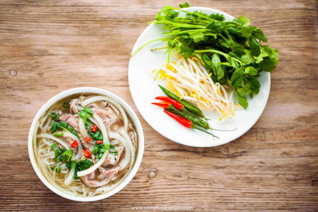 Vietnamese Pho noodle soup with a vegetable side dish