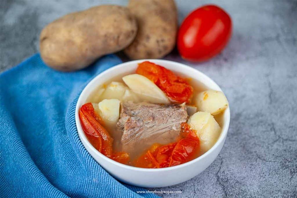 tomato potato pork bone soup in a bowl with blue towel