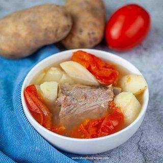 tomato potato pork bone soup in a bowl with a blue towel