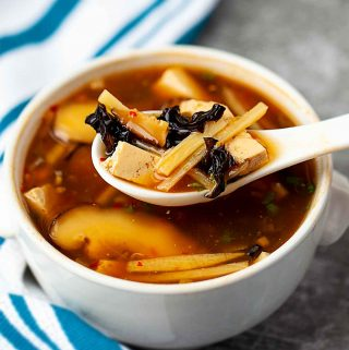 a scoop of hot and sour soup on a white spoon