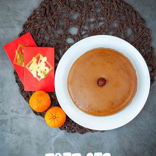 Chinese New Year rice cake nian gao with red pocket and mandarin oranges