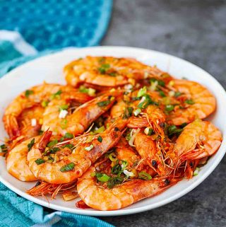 chili garlic shrimp on an oval white plate with blue towel
