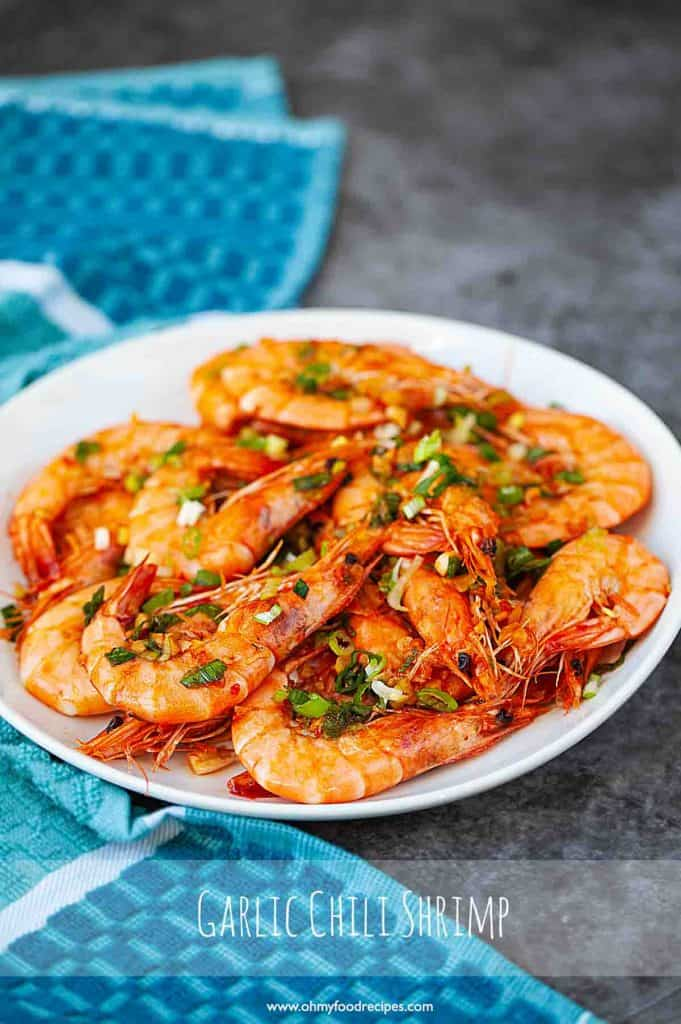Asian style chili garlic shrimp on an oval white plate with blue towel