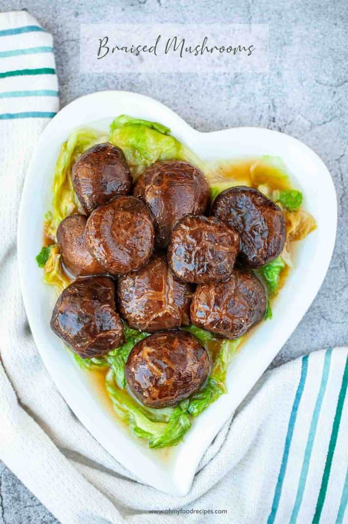 braised Chinese shiitake mushrooms on lettuce on a white heart shaped plate
