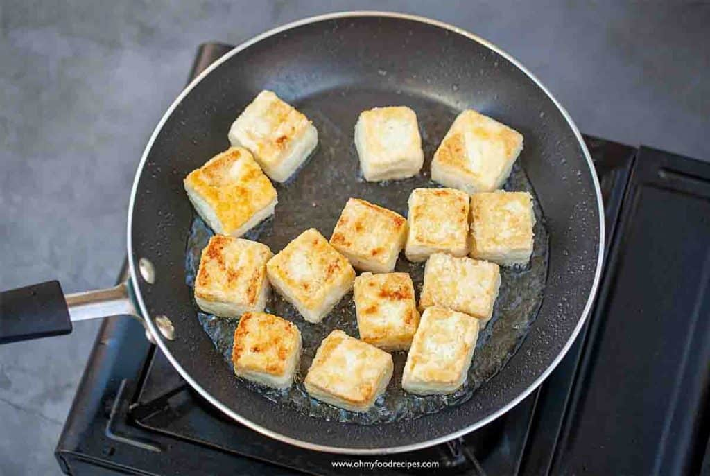 golden brown pan fried crispy tofu in the non-stick pan