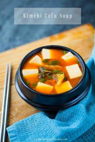 Korean kimchi tofu soup in a black pot with chopsticks