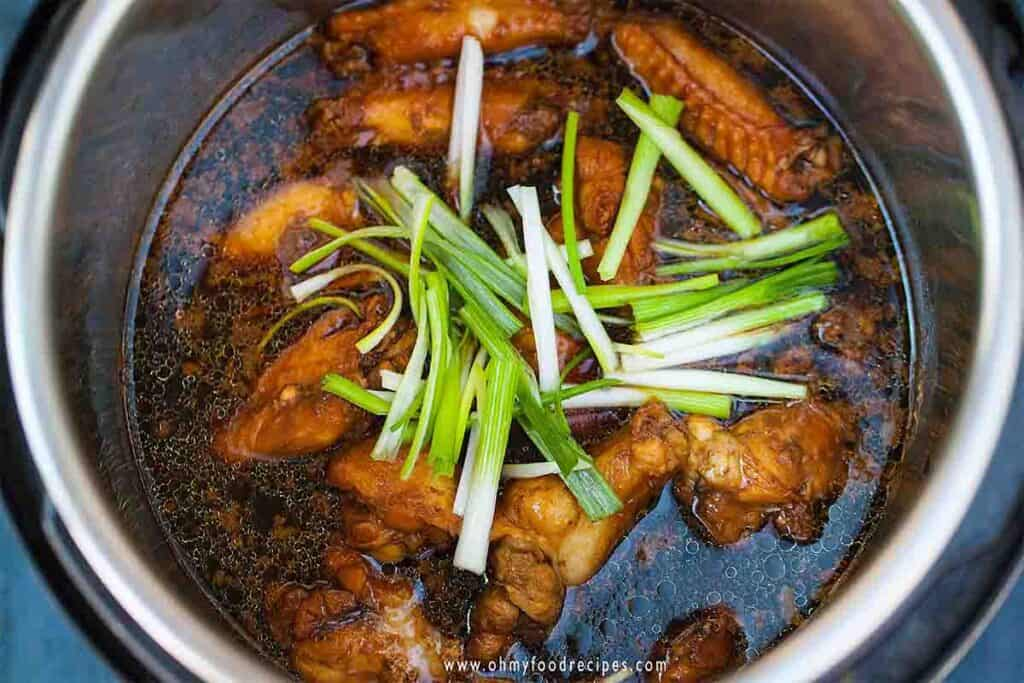 cooked soy sauce chicken wings in the instant pot with green onion on top