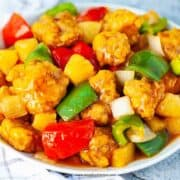 Chinese sweet and sour pork on a white plate with a checked towel