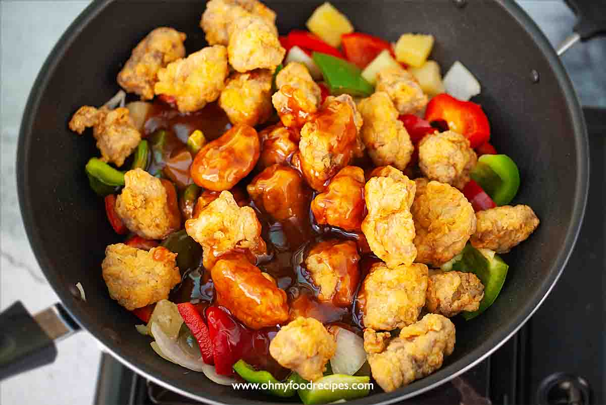 sweet and sour sauce pour over the deep fried pork with vegetable in the wok gu lou yuk