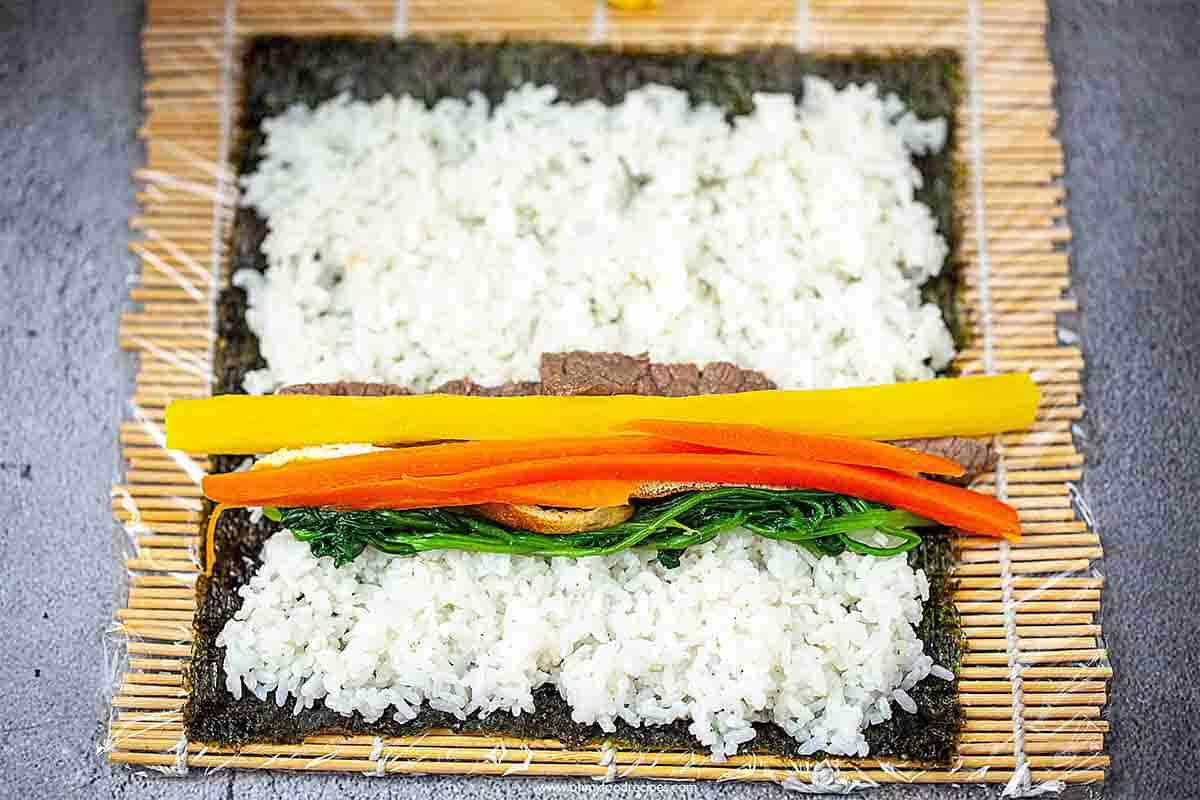 fillings on the rice over the seaweed and bamboo rolling mat