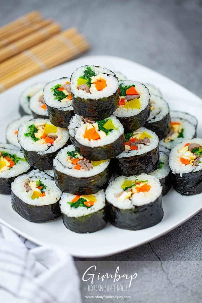 side view sliced korean kimbap stack up on a white plate