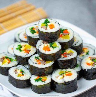 sliced gimbap/ kimbap stack up on a white square plate