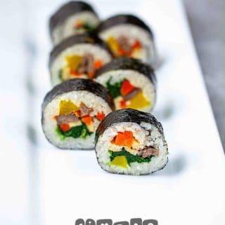 sliced korean kimbap sushi roll on a long white plate