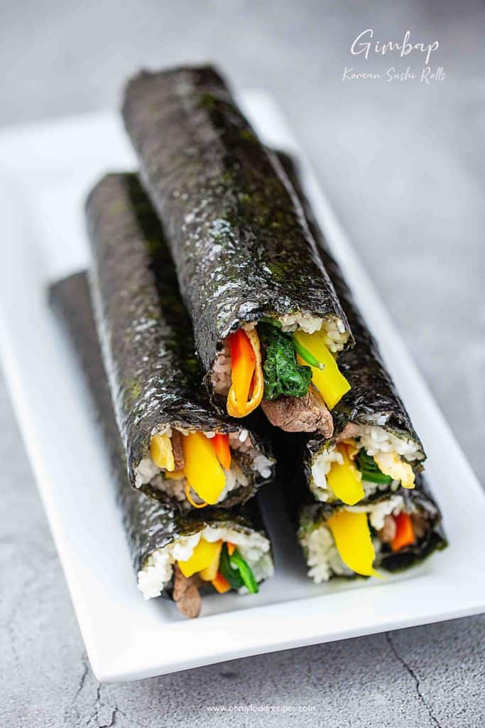 gimbap or kimbap sushi rolls stack up on a white plate
