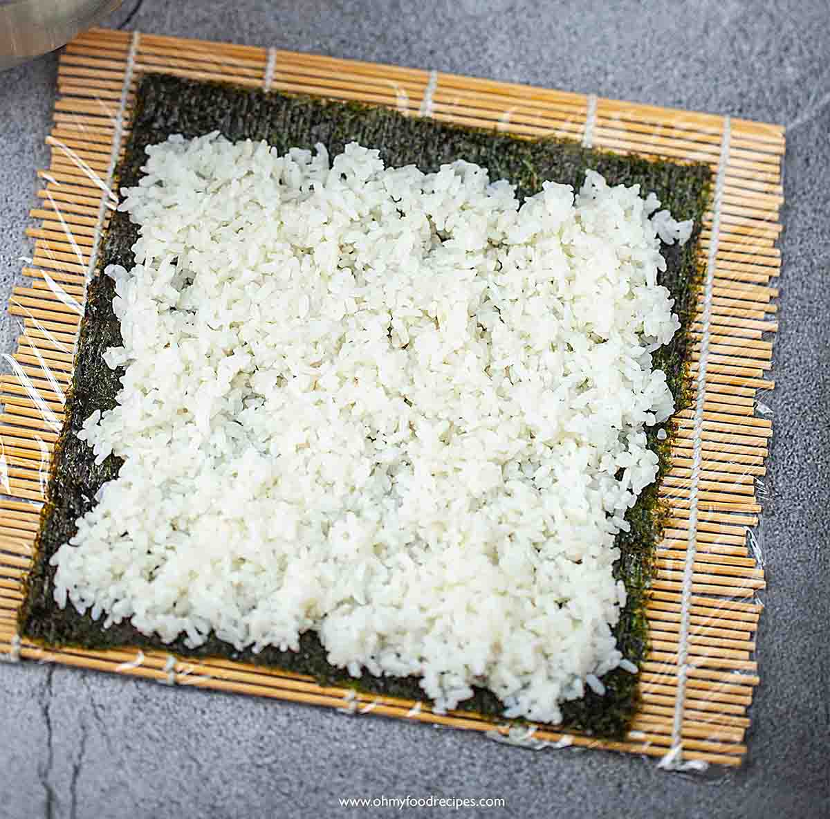 cooked rice on nori with bamboo rolling mat