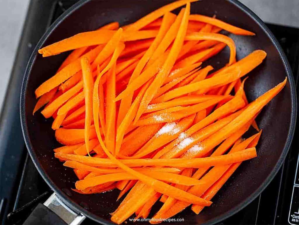 Stir fry carrot strips in the pan