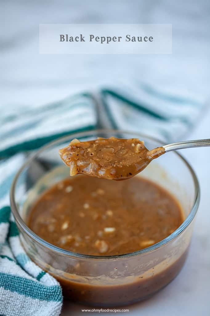 Black pepper sauce on a sliver spoon