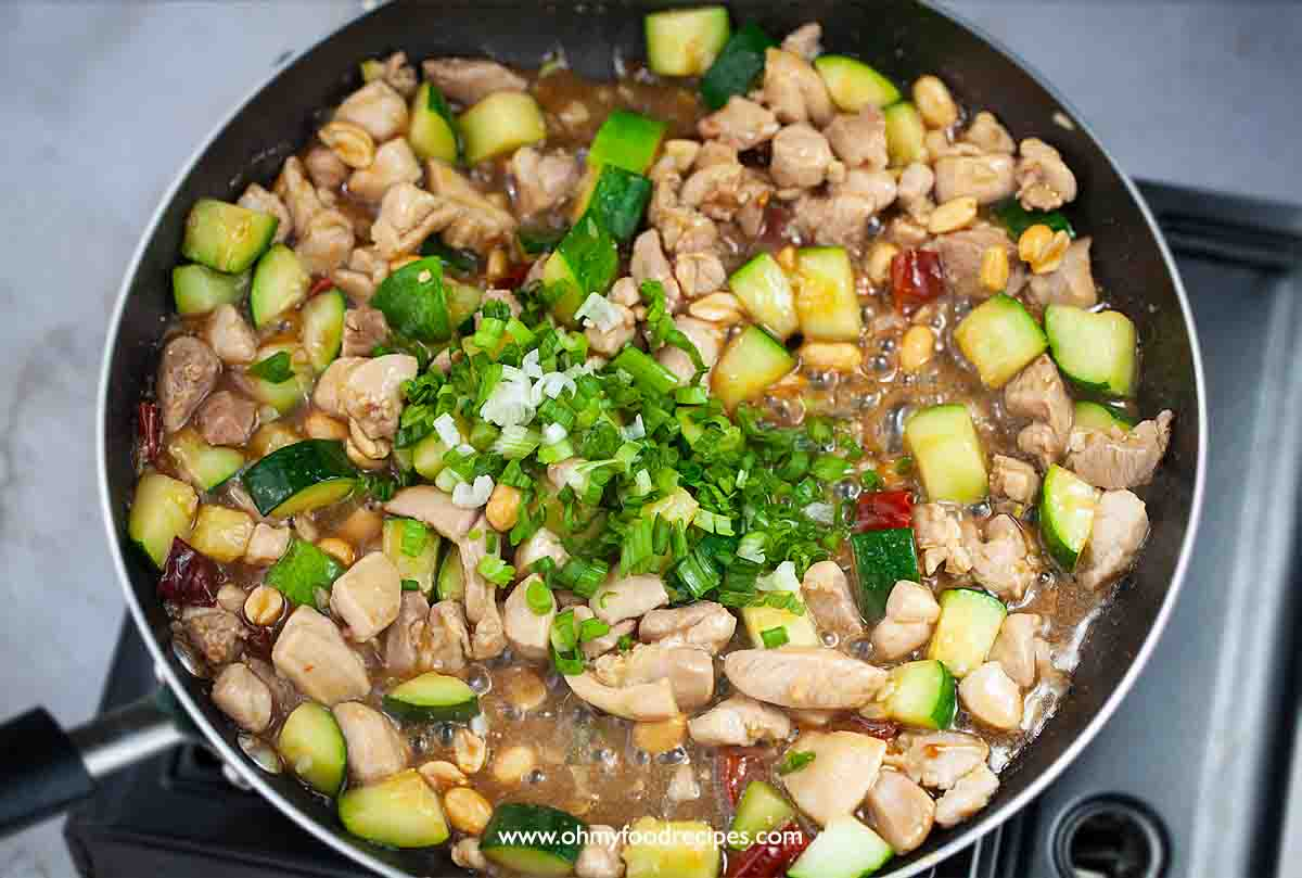 green onion added into the pan kung pao chicken stir fry