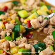 Chinese kung pao chicken on the silver spoon close up