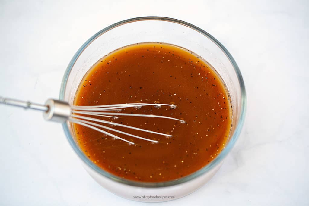 sauce mixed in a glass container with a whisk