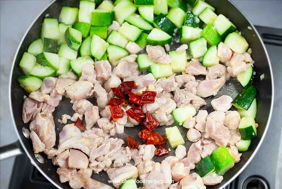 dried chili peppers with chicken and zucchini in the pan