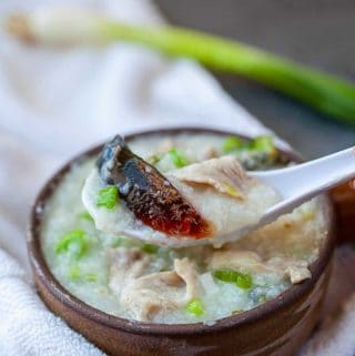 congee with pork and preserved egg on a white spoon and in a clay bwl