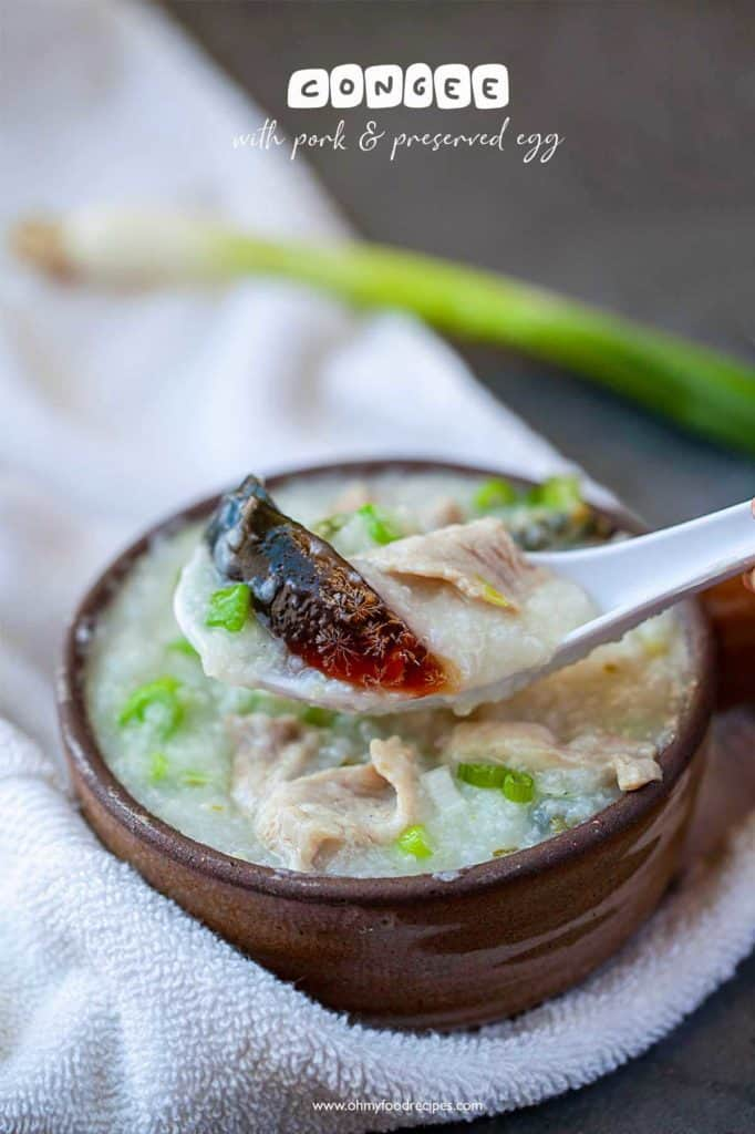 congee with pork and preserved egg on a white spoon and in a clay bowl