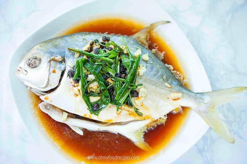 steamed whole fish on a white plate