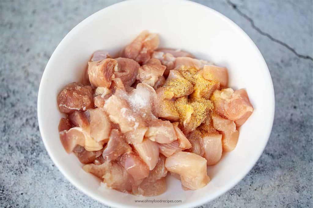 Marinate chicken thigh in a white bowl
