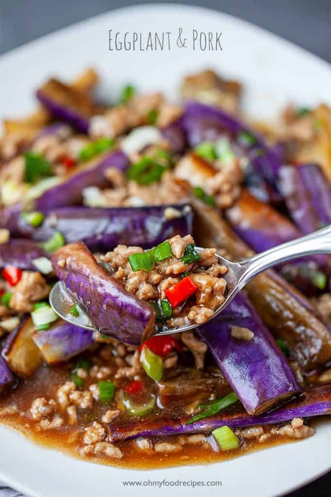 a scoop of eggplant and pork stir fry on a silver spoon