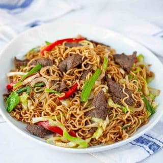 instant ramen noodles stir fry with beef on a white plate