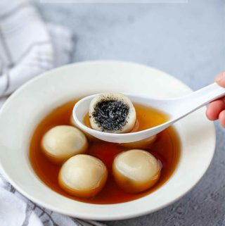 tang yuan with black sesame filling on a spoon