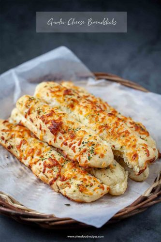 garlic cheese breadsticks on a basket tray with a paper